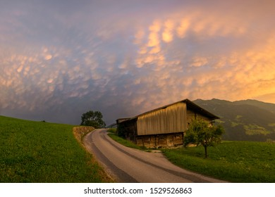 Stunning landscape image of a cottage along a country road in the mountains of Austria. Colorful storm clouds as background.