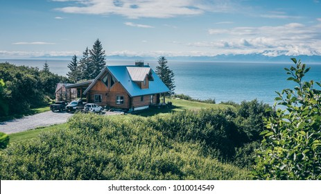Stunning landscape of a nice cabin in Alaska overlooking the ocean from a green hill