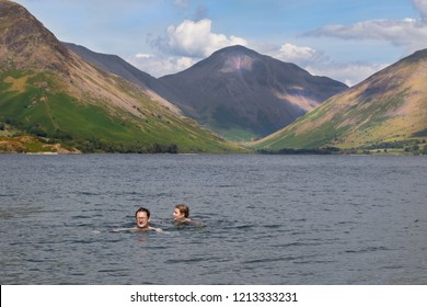 Stunning landscape view of Wast Water and fells in the Lake District National Park, UK. Two people relaxing and swimming in the lake and enjoying a beautiful sunny day