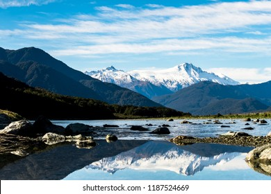 Stunning landscpae of the reflection of the snow mountain on the river. Blue sky and some cloudy.