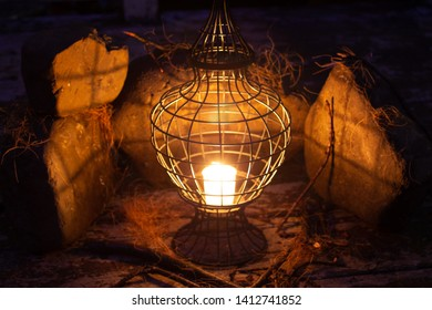 Stunning Lantern with a candle inside. Orange glow in the rocks in the background.