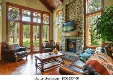 Stunning living room design includes a stone wall fireplace, brown leather sofa with a curved cocktail table facing a pair of leather armchairs with nailhead trim atop hardwood floor. Northwest, USA