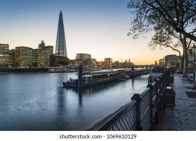 Stunning London City skyline landscape at night with glowing city lights and iconic landmark buldings and locations