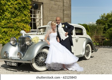 A stunning looking bride and groom next to a vintage wedding car