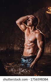 Stunning man with muscular body taking shower outdoors. Man in jeans and naked body in sea water.