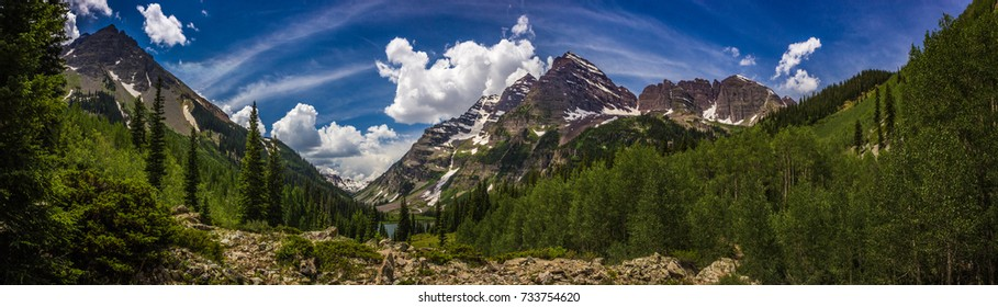 Stunning Maroon Bells and Crater Lake in Snowmass Wilderness in Aspen, Colorado with a blue sky and clouds in summer