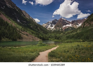 Stunning Maroon Bells peaks and trail leading to Maroon Lake in summer near Aspen, Colorado