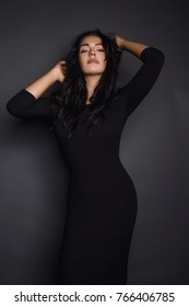 Stunning model in elegant dress posing provocatively at camera.