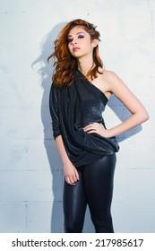 Stunning Model with Long Wavy Auburn Hair Against White Brick Wall