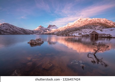 Stunning  morning light, over snow capped Cradle Mountain.With Dove Lake and Historic Boat Shed in the foreground.Cradle Mountain Lake St Clair National Park.Central Highlands of Tasmania.Australia.