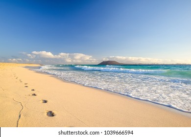 Stunning morning view of the islands of Lobos and Lanzarote seen from Corralejo Beach (Grandes Playas de Corralejo) on Fuerteventura, Canary Islands, Spain, Europe. Beautiful footprints in the sand.