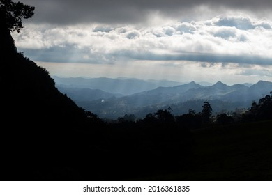 Stunning mountain landscape with forest silhouettes sunbeams and mountainrange at background in cloudy day