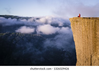 Stunning natural view. Rock Preikestolen over Lysefjord. The girl sight seeing the famous Norwegian landmark