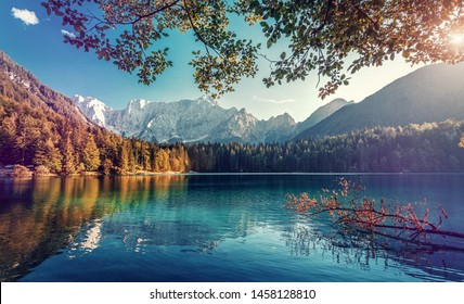 Stunning nature Landscape. Fantastic sunset scene. popular travel location, Lago di Fusine with Mangart peak on background under sunlit. Amazing colorful Scenery. Beauty of World.