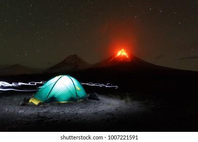 Stunning night mountain landscape of Kamchatka Peninsula: illuminated tourist camping on background fantasy eruption volcano, light from headlights around tent. Russian Far East, Klyuchevskoy Volcano