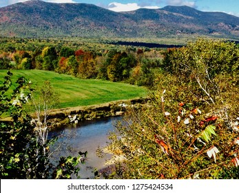 Stunning North Conway, New Hampshire in fall with gorgeous mountains, green valley, trees, colorful autumn foliage & the Saco River in view