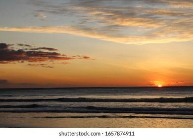 Stunning orange and pink sunset on Avellanas Beach in Costa Rica.