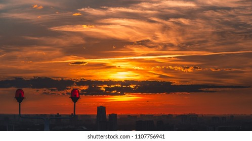 Stunning orange sunset in urban settings filmed from the high point from skyscraper with silhouetes of buildings below, the sun hided by the cloud, red signal lights set on the roof in the foreground