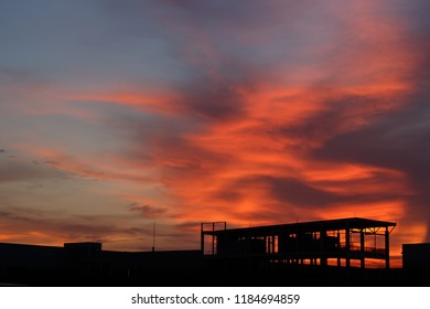 Stunning orange sunset in urban with silhouetes of buildings