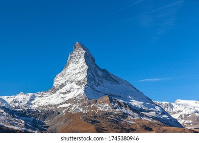 Stunning panorama view of the famous Matterhorn peak of Swiss Alps on sunny autumn day with snow and blue sky, from the train staion Riffelberg, Valais, Switzerland