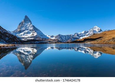 Stunning panorama view of the famous Matterhorn and Weisshorn peak of Swiss Pennine Alps with beautiful reflection in Riffelsee lake on sunny autumn near train station Riffelberg, Valais, Switzerland
