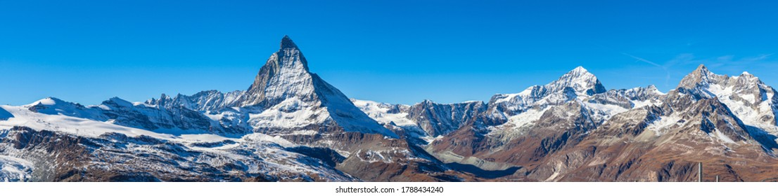 Stunning panorama view of the famous Matterhorn, Weisshorn and Pennine Alps on Swiss Italien border on sunny autumn day with snow and blue sky, from Gornergrat station, Valais, Switzerland