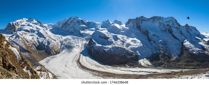 Stunning panorama view of the Gorner Glacier and Monte Rosa massif, Lyssskamm peak on Swiss Italian border from Gornergrat station on sunny autumn day with snow and blue sky, Valais, Switzerland