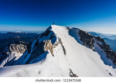 Stunning photo of a climber climbing sharp ridge of an alpine peak. Mountaineer on a summit winter climb. Adventure and extreme ascent in the slovenian Alps. Outdoor activity, winter hiking.