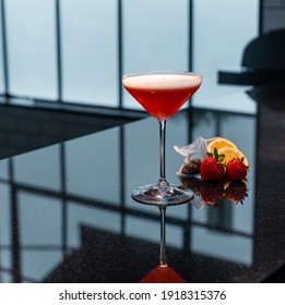 Stunning pink cocktail in a martini glass on bartop counter mixology fine dining