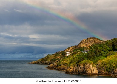 Stunning rainbow rising after the rain above the beautiful Howth Head green cliffs, in Dublin, Ireland. Seaside landscape on the Irish coast on a stormy weather day.