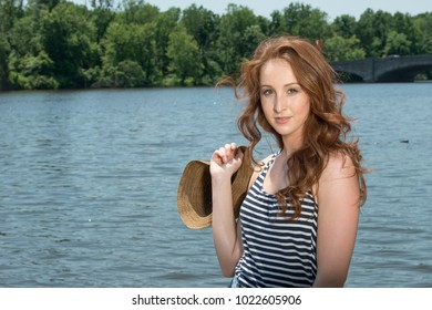 Stunning redhead woman in denim cutoff mini-skirt, hat,  and  striped tank top poses near river in bright sunshine - summer fun