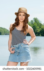 Stunning redhead woman in denim cutoff mini-skirt and hat poses near river in bright sunshine - summer fun