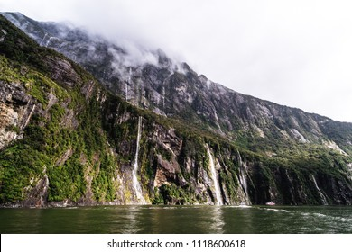 A stunning scene of nature with many waterfalls from the high mountain at Milford Sound, New Zealand.