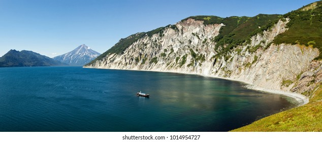Stunning scenery autumn panorama landscape, top view of steep mountainous coast of Pacific Ocean on unique nature of Kamchatka Peninsula on sunny day with clear blue sky. Eurasia, Russian Far East