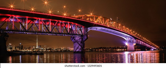 Stunning scenery of illuminated Auckland Harbor Bridge with Sky tower and the city at night. Solar lighting systems. Auckland, New Zealand.