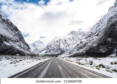 The stunning scenery of a rocky mountain and trees covered with a white snow. A road to Milford Sound. A filmed while driving.