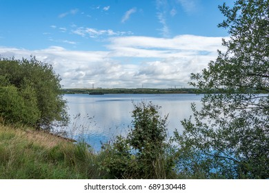 stunning scenic view of the lake at Chase waters in cannock. green bushes and trees in foreground with large blue lake and blue sky with white fluffy clouds