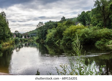 stunning scenic view of the river severn with the ironbridge in the distance, green bushes and trees can be seen both sides of the river.