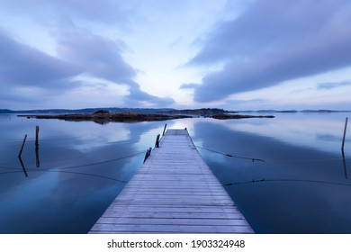 Stunning seascape in cool colors with bridge, rocky islands, and purple clouds in a symmetrical composition on an early morning in Sweden