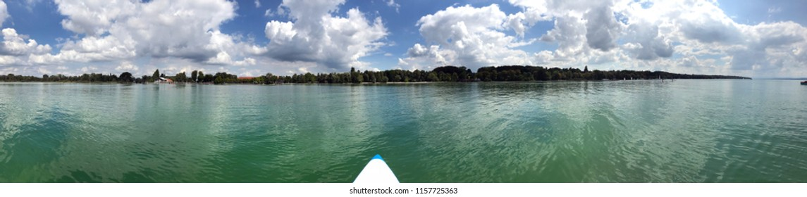 Stunning seaside panorama of Ammersee with a stand up paddle board on a sunny day with blue sky and clouds, Germany