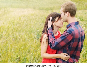 stunning sensual outdoor portrait of young stylish fashion attractive couple in love kissing in summer field