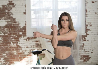 Stunning and sexy young woman (Fitness model) in studio vintage exercise bike in background stretching arms