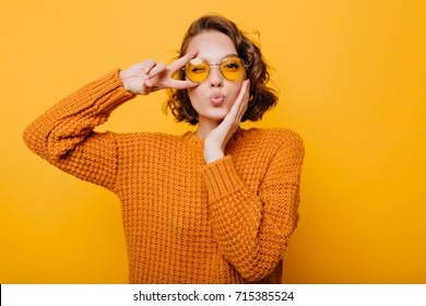 Stunning short-haired female model posing with kiss face expression on yellow background. Close-up portrait of stylish european girl standing with peace sign in front of wall.