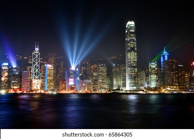 Stunning sight seeing of the Victoria harbor in Hong Kong illuminated at nighttime with futuristic buildings and colorful lights.