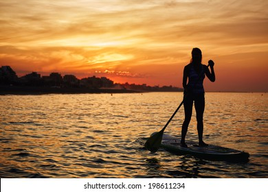 Stunning silhouette of a beautiful girl floating on on the surfboard at amazing orange sunset over the sea