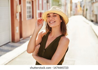 Stunning smile on sunhat girl standing in street, portrait
