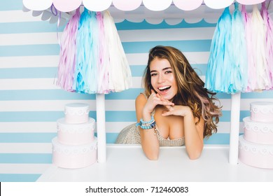 Stunning smiling girl with big kind eyes selling tasty cakes standing behind pink counter. Close-up portrait of attractive joyful young woman posing with sweets on blue striped background.