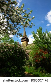 A stunning spring day with apple trees and lilac in bloom in Maramures, Romania. The traditional high wooden church with an enormous spire is the symbol of Maramures architecture. Churchyard in bloom