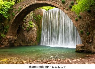 Wunderschöne Frühlingslandschaft. Paleokarya, alt, Stein, Bogenbrücke, zwischen zwei Wasserfällen. Präfektur Trikala, Thessalien, Griechenland