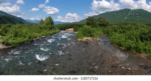Stunning summer panoramic landscape of Kamchatka Peninsula: view of stream clear water of mountain Paratunka River and green forest on hills along riverbank on sunny day. Eurasia, Russian Far East.